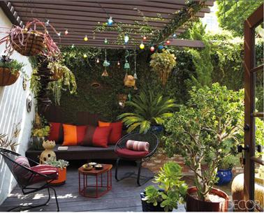 Des couleurs chaudes pour une terrasse intime sous auvent en bois