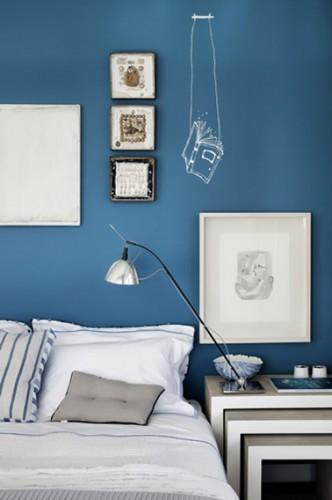 Déco chambre bleu et gris : Aux murs une peinture bleu Cyclade, table de chevet gigogne et cadres photo gris perle mis en valeur par les touches de blanc
