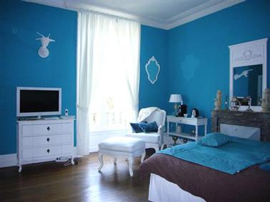 Une chambre bleu qui affiche la couleur sur ses murs avec une peinture bleu turquoise intense en contraste avec les meubles blanc. Le couvre lit chocolat et le parquer de chêne apportent une touche de tons chauds. Peinture Tollens