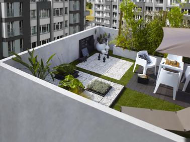 Déco de terrasse en ville ambiance zen et minimaliste avec un sol couvert de dalles de gazon synthétique et carrés de galets blanc.