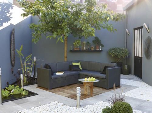 Déco terrasse zen aménagée avec un sol en dalles de bois pour le coin salon de jardin et de galets et carreaux de pierre grise en damier. Le salon de jardin gris anthracite s'harmonise avec le gris des matériaux du sol. Dalle bois Douglas 50X50 Leroy Merlin