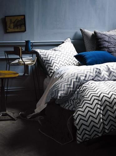 Une peinture chambre couleur délavé et des tons de bleu marine à bleu klein pour le linge de lit uni et à rayures. La table de chevet jaune moutarde révèle la subtilité des jeux de couleurs bleu