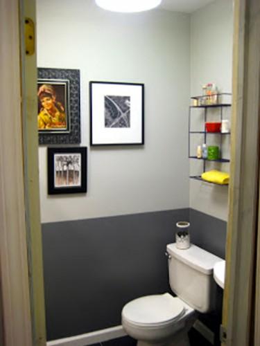 Peinture WC de deux couleurs : gris anthracite pour peindre le soubassement et gris perle sur le haut des murs. Cuvette WC et lave-mains blanc. Etagères en fer pour le rangement des accessoires