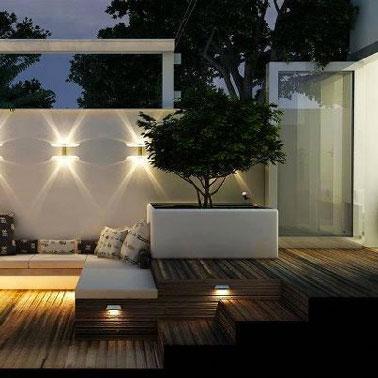 Ambiance zen sur la terrasse en bois autour d'un canapé aménagé dans sol en teck surélevé.