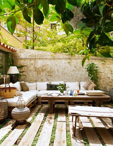 Salon de jardin en palette fabriqué pour une installation en L sur 2 murs de la terrasse en bois. Assortie, une table basse en palette dont le plateau plein est assemblé grâce à des tasseaux fixés par le dessous.