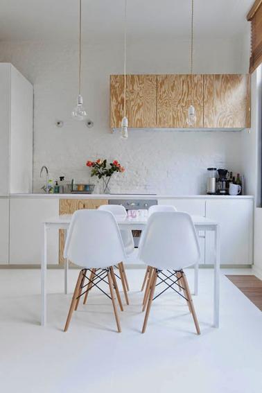 Pour repeindre les meubles de cette cuisine, on a choisi d'alterner les façades blanches et bois blond pour donner du rythme à la pièce. Dynamique renforcée par les chaises coques dans le même code couleurs et bois clair verni pour les pieds et l'assise blanche.
