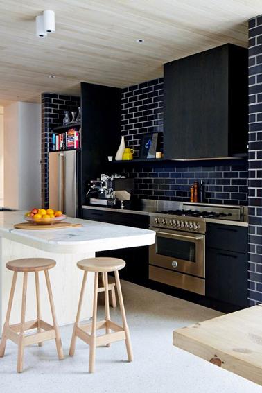 Une bonne idée pour refaire sa cuisine pas cher, repeindre les meubles en noir et le carrelage de la crédence et refaire les joints en blanc