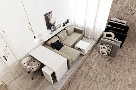 espace salon bureau dans studio monté sur petite estrade pour séparer l'espace de la cuisine ouverte