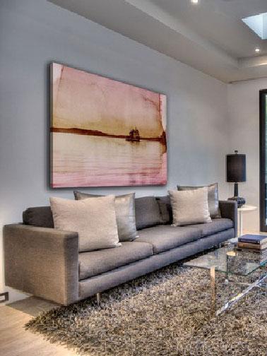 Dans ce salon à l'architecture moderne, le grand diptyque sur boispeint avec de subtiles nuances de beige rosé au dessus du canapé taupe, confirme combien l'association de tonsneutres et de couleurs naturelles peut adoucir le salon.