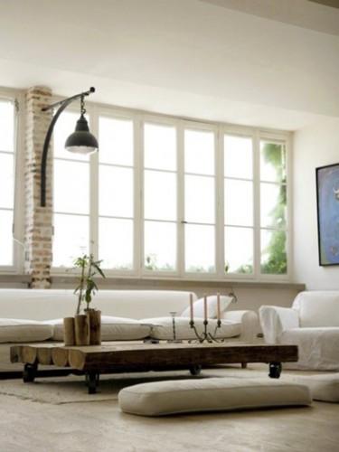 Pour ce salon aménagé avec goût dans un ancien atelier les couleurs et matériaux naturelles sont à l'honneur avec une couleur lin en deux tons pour peindre murs et cadre fenêtre et soubassement. Canapé cuir blanc, table en bois réalisé par un artisan.