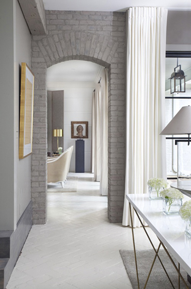 Nuance de peinture gris dans un salon en enfilade de la salle à manger. Le sol blanc et les rideaux couleur lin font un lien entre les deux espaces