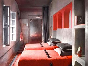 Couleurs décoration chambre béton ciré gris aux murs linge de lit couleur rouge et gris anthracite dans un esprit riad marocain zen plein de charme