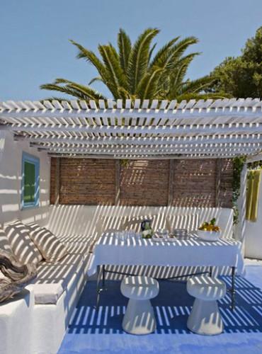 Superbe ambiance sous cette pergola bois d'une maison grec. Sur le sol en ciment blanc est peint un grand tapis bleu qui sublime le blanc des banquettes et de la pergola.