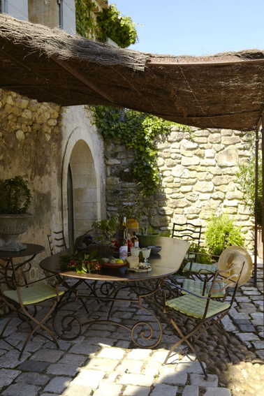 Pergola terrasse en brande de bruyére installée devant maison provençale pour protéger la terrasse du soleil avec salon de jardin