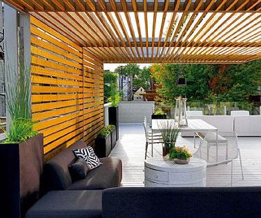 De l'ipé pour la pergola en bois d'une terrasse design abritant le coin salon et table de jardin. Le soir le plaisir de la terrasse prend ses quartiers dans les grands canapés face au jardin.