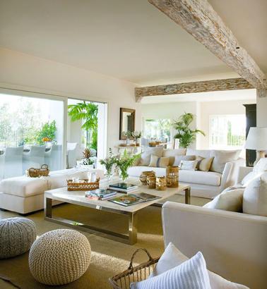 Dans un salon moderne aux larges baies vitrées, seul le vert tendre des plantes d'intérieur pour relever la couleur lin et blanc des murs, du sol et des canapés pour un résultat plein de fraicheur