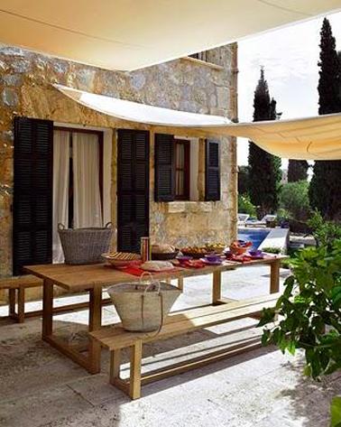 Une voile d'ombrage pour compléter la protection apporter par le store banne sur la terrasse d'une maison en U