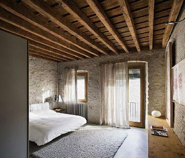 Dans un appartement moderne, belle réalisation pour une chambre zen avec des murs de pierres et briques blondes. Profitant d'une situation au dernière étage, le plafond est mis a brut pour profiter de l'aspect chaleureux des poutres apparentes et du plancher
