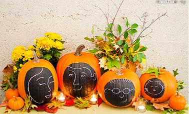 Décoration de citrouilles d'Halloween avec des dessins de visages de la famille faits à la craie et intégrées dans une composition de branchages, feuilles rouge et bougies