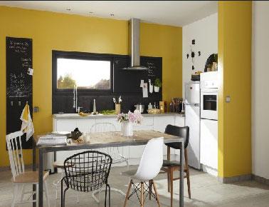 Conviviale et bien aménagée une cuisine blanche boostée par une peinture couleur jaune sur le mur du linéaire plan de travail  qui offre à la pièce un sérieux gain de luminosité. Originale, le cadre de fenêtre élargi peint en noir pour faire office de crédence. Une idée à retenir pour une cuisine moderne.