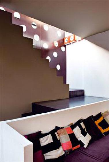 Dans ce salon ouvert sur l'escalier, le mélange de aubergine, gris et terre doré appliqués sur les murs délimite chacune des zones. L'intensité des couleurs est renforcée par le muret blanc qui accueille la banquette réalisée sur mesure où l'on retrouve la couleur aubergine pour le tissu des coussins d'assise.