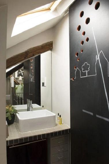 Dans cette petite salle de bain, la cloison ardoise dissimule les WC et la douche à l'italienne. Une colonne de rangements prend place sous la vasque et un miroir coupé aux mesures agrandit l'espace