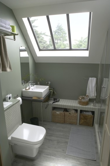 Une petite salle de bain de 4.5 m2 à l'aménagement pratique. Lumineuse grâce au puits de lumière, plan vasque plutôt qu'un meuble et banc maçonné prolongeant la douche.