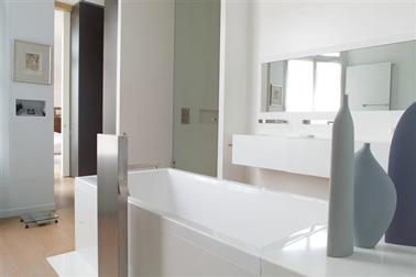 Gris et blanc, deuxcouleurs peinture salle de bain pour une ambiance déco où sobriété et esprit intemporel sont les maîtres mots. Une peinture d'un blanc pur couvre les murs de la douche et celui des vasques. Sur les autres murs, une peinture couleur gris bleuté apporte un léger contraste avec les sanitaires blanc brillant. La paroi de douche en verre teinté, les vases aux tonalités grises et vert céladon et les accessoires inox complètent la palette couleur douce de cette salle de bain zen. Couleurs peinture nuancier Tollens.