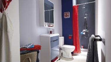 Du rouge et du bleu, cette petite salle de bain étroite et longue joue sur les couleurs. Pour agrandir l'espace, la douche à l'italienne est aménagée à la perpendiculaire