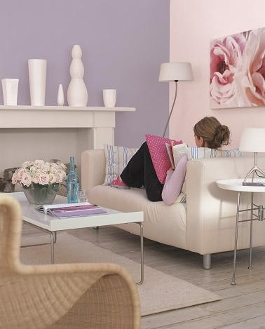 Dans ce salon, la peinture couleur parme se marie à merveille avec le canapé beige et la cheminée gris clair. Une ambiance sereine, douce et moderne, propice à la détente !