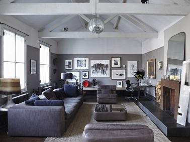 Une peinture grise dans un salon cosy appliquée sur la partie basse des murs pour mettre l'accent sur les poutres et le plafond peints en gris plus clair. Face au canapé gris anthracite la cheminée peinte en brun foncé apporte sa touche de couleur chaude. Peinture couleur gris Chemise Farrow Ball