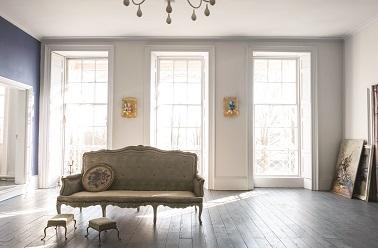 Entre gris et lin cette teinte de peinture dégage dans le salon une ambiance en tout point paisible. Un parquet chêne, un pan de mur peint en bleu, un canapé Louis XV et le chic prend place dans le salon. Peinture Farrow & Ball couleur Dimpse.