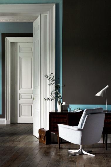 Dans ce salon, le gris intense de la peinture est souligné d'un bleu lumière pour repeindre le soubassement et l'encadrement des portes blanches. Design, la déco de ce salon  s'organise autour des couleurs et des meubles modernes mis en contraste.  Peinture couleur Gris Attic II, Bleu Sky Blue Litlle Greene.