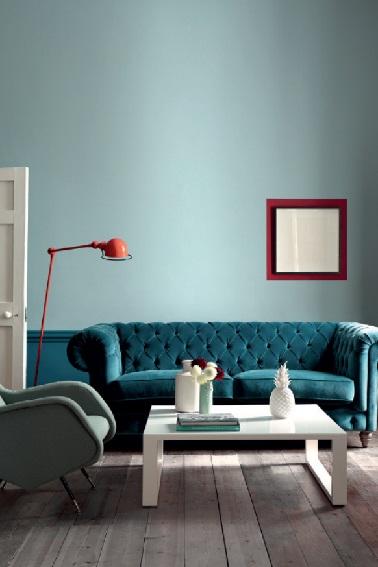 Ce salon adopte une peinture bleu sur ses murs. Pour peindre le haut du mur une teinte de bleu gris pour sa douceur contraste avec le bleu du soubassement coordonné au canapé de style. Avec du rouge et blanc pour les accessoires, un petit salon tendance rétro chic. Peinture Little Greene.