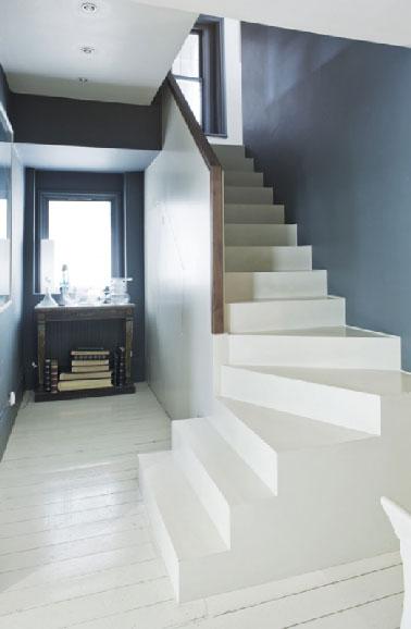 Une entrée relookée en bleu et blanc avec la peinture pour sol Farrow & Ball qui s'applique de la même façon sur le parquet du couloir que le béton de l'escalier. Avant de repeindre le parquet, les lames sont débarrassées de leur vernis afin d'obtenir un bois nu et lisse. Le bois est  ensuite recouvert d'une couche d'impression pour Sols Bois Farrow & Ball avant d'appliquer La peinture en deux couches. Sur le béton brut de l'escalier, la même peinture est utilisée après un dépoussiérage et lessivage du support. Réf peinture sol : Off-White No.3 Floor Paint. Peinture bleu des murs : Down Pipe No.26 Estate Emulsion de Farrow & Ball