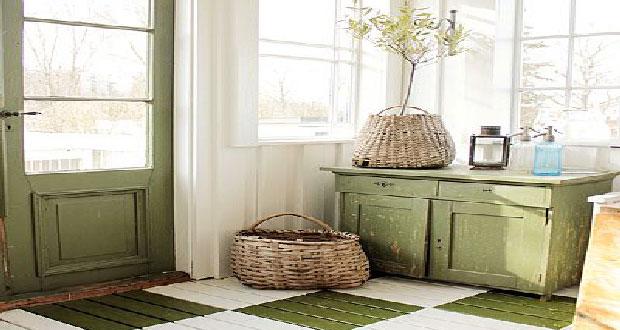 Décoration accueillante pour l'entrée d'une maison de campagne aménagée avec un meuble de rangement et un sol en bois repeints en vert et lin.