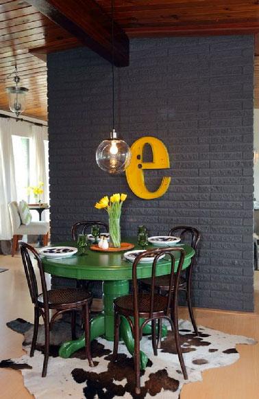 Astucieux le recours à une cloison pour mixer les ambiances déco dans un salon salle à manger. Aménagée derrière une cloison imitation brique, la salle à manger style bistro laisse le salon affirmer une décoration plus traditionnelle.