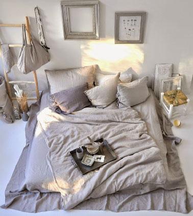 une chambre zen et de rêve pour s'offrir une déco cocooning avec son lit au niveau du sol, les tables de chevet en bois et les tons lin et mordoré de la couette et des coussins