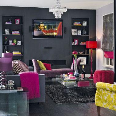 Du gris anthracite sur le mur de la cheminée, une peinture gris clair sur les autres murs avec un canapé gris et des accessoires rouge et jaune pour la décoration d'un salon moderne et cosy