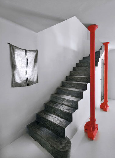 Soulignant l'architecture de la cage d'escalier grise et blanche, les marches peintes en gris anthracite et les 2 piliers rouge vif invitent à monter à l'étage sans précipitation pour profiter de l'ambiance épurée qui règne dans l'entrée.