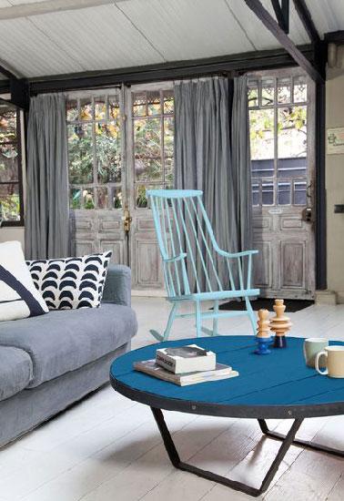 Une peinture en 2 teintes de bleu pour repeindre un fauteuil et une table basse dans un salon  aux murs et rideaux gris crée un contraste dynamique à peu de frais. Peinture couleur bleu récif pour le fauteuil en bois, couleur Lumière d'Azur satin sur le plateau de table basse en bois et noir satin pour les pieds en fer. Peinture Rénovation Design & Vous Tollenschez Castorama.