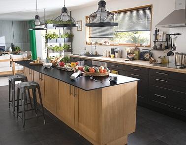 Cette cuisine industrielle familiale table sur des basiques déco. L'îlot central en bois, les suspensions et les tabourets suffisent pour lui donner un style unique.