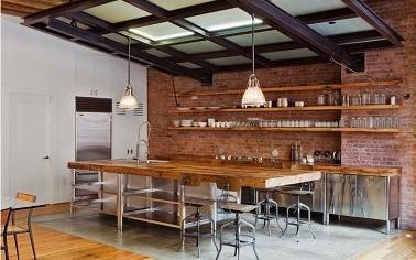 Dans cette cuisine industrielle, l'ambiance chaleureuse prédomine. Les briques rouges, le plan de travail en bois et l'acier se marient dans un esprit loft convivial.