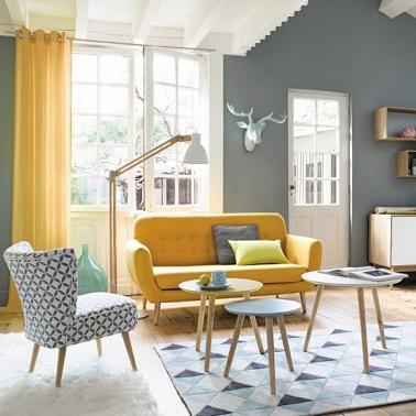 Dans ce petit salon, l'aménagement déco se fait à l'aide meubles arrondis très délicats et rétro. Le canapé jaune sur pied égaye la pièce et rend l'espace plus moderne.