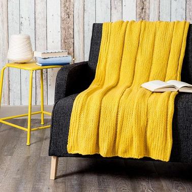 Du jaune flashy sur un plaid tricoté en laine signé Maisons du Monde