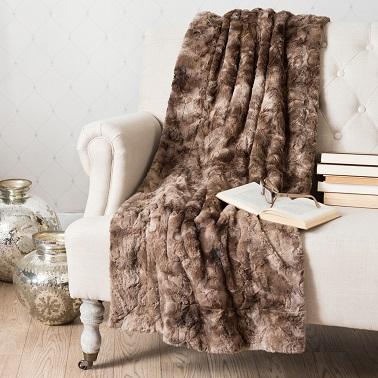 Dans une chambre ou un salon cocooning, un plaid signé Maisons du monde en fausse fourrure, en tissu ou en tricot aide à se réchauffer lors des froides soirées d'hiver.