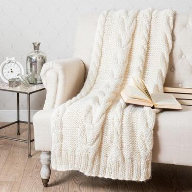 Un plaid tricoté en grosses mailles couleur blanc cassé.