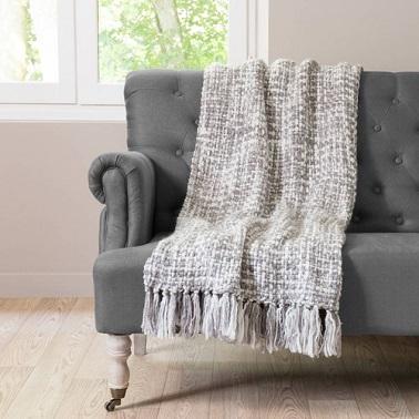 Un plaid en tricot couleur gris argenté avec pompons.