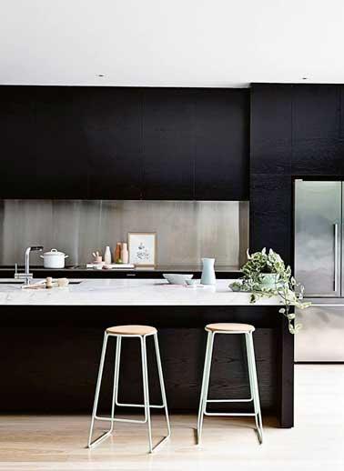 Une crédence en alu brossé installe la déco design de cette cuisine noire. Elle prend toute sa valeur placée entre des meubles de rangement en bois noir.