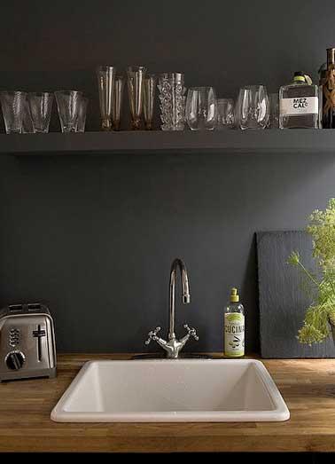 Déco luxueuse pour la crédence en peinture noir mat de cette cuisine contemporaine. Verres et objets inox apportent lumière et intensité à la couleur noir.